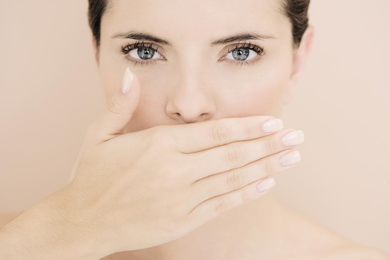 Frau verdeckt mit der Hand Ihren Mund